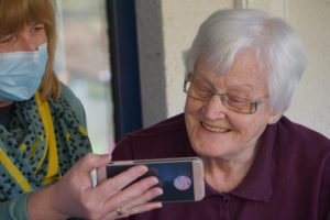 Narrative Medicine Care image showing a care Supporter holding a smartphone up for an elderly woman to see as they talk.